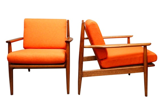 Mid century curated pair danish lounge chairs with orange cushions