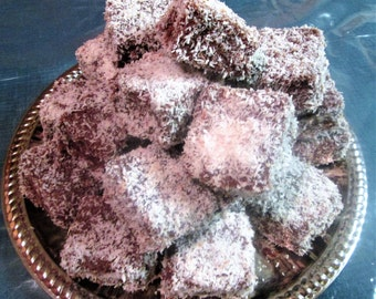 Lamingtons. Sponge Cake covered in Chocolate, and rolled in Dessicated Coconut.  Favorite Dessert of our Aussie friends. 1 doz per order