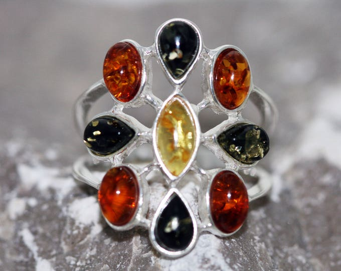 Large Baltic amber ring. Nine pieces of amber in three different shades fitted in sterling silver setting. Statement ring.