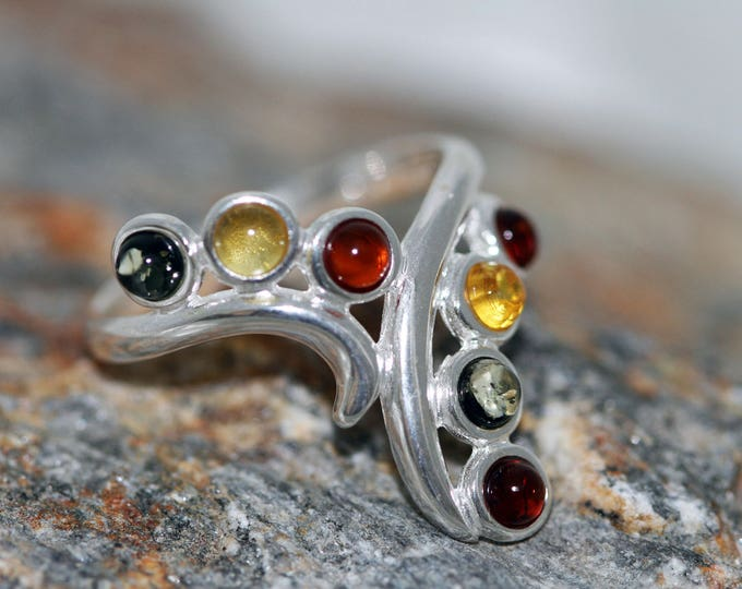 Baltic amber ring. Seven pieces of amber in three different shades fitted in sterling silver setting. Statement ring.