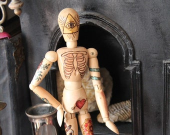 Articulated wooden mannequin decorated in a tattoo style