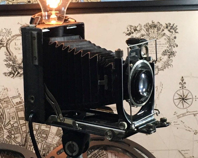 Vintage upcycled lighting camera. 1908 Kodak plate camera lamp om tripod.