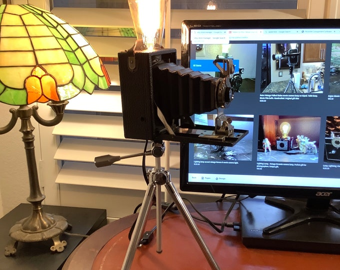 Vintage upcycled lighting camera. 1900s plate camera lamp on tripod.