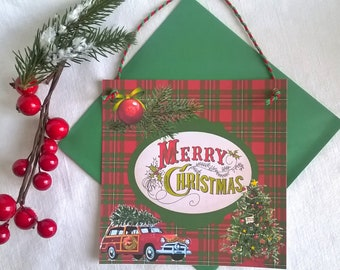 Card hanging Christmas traditional theme on Plaid background with green envelope