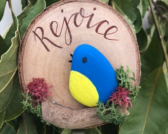 Hanging Ornament Rejoice Pebble Bird on a driftwood branch mounted onto a log slice.