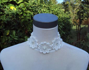 Around the neck cotton flowers, embroidered with beads and white ribbons