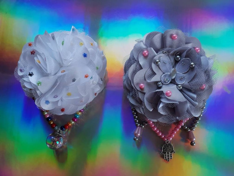 Large grey flower hair fascinator decorated with a white butterfly a hand of hamsa and pink teardrop pearls on pink and grey pearl chains