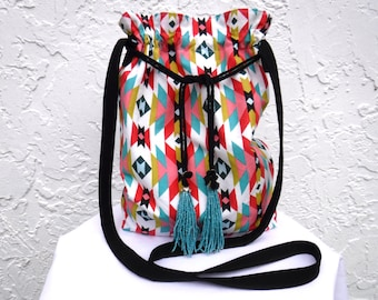 Southwestern print drawstring crossbody bag. Purse with geometric/Aztec print has turquoise beaded tassels. Show off your desert boho style.