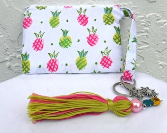 Pineapple-print wristlet with keychain tassel purse charm. Pink and green pineapples act as your wallet or hold your phone. Fun pouch gift.