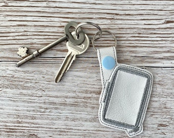Machine embroidery hoop key fob and USB memory stick tag, made from embroidered faux leather.