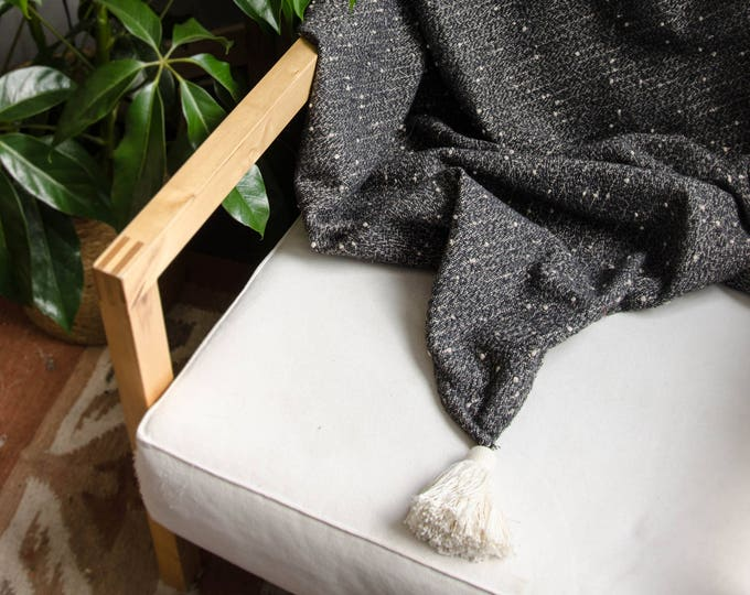 Black and white throw blanket with white tassels.