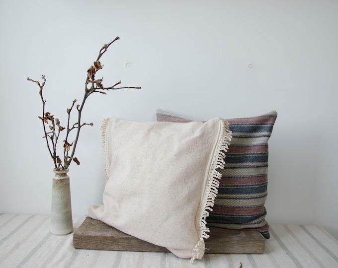 Decorative cushion cover. White woven natural fiber cream fringes