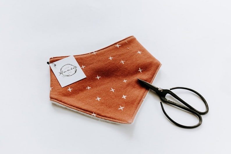 Sketched Swiss cross bone on rust red Organic cotton knit drool bib with softer