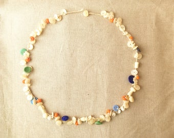 Handmade necklace from vintage shell beads, glass buttons, plastic buttons and glass beads strung on linen thread