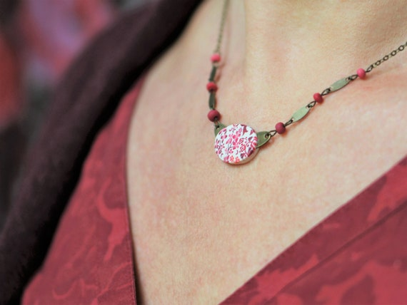 Short necklace with a handmade red floral pattern oval on an antique brass chain, 'Astrance' series'