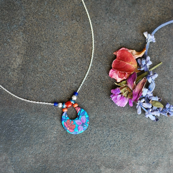 Purple wax and terracotta floral pattern pendant on silver chain, 'Clivia' collection
