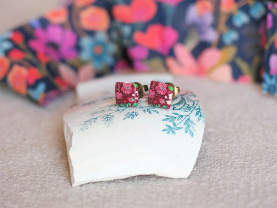 One pair of square stud earrings with purple and pink floral patterns