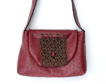 Burgundy faux ostrich leather bag with macramé embellishment and denim interior.