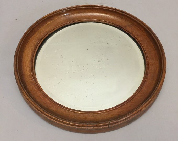 Old foxed round mirror in wood frame