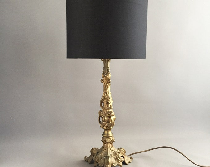 gold metal ornate lamp with black shade