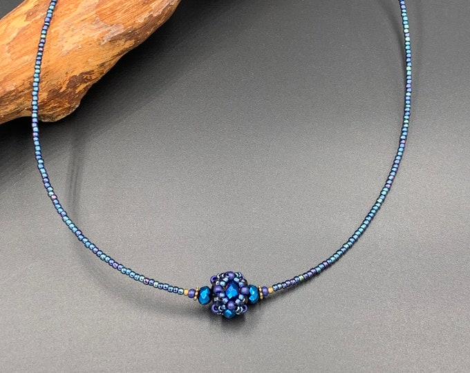 Short handmade beaded necklace with hand threaded glass ball.