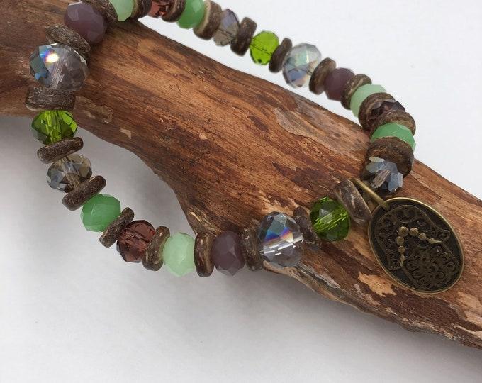 Handmade beaded bracelet with coconut wood beads. With Hamsa hand the Fatima pendant.