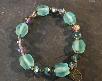 Handgemachtes Armband in Aquafarben aus Glasschliffperlen und Glasperlen mit Messing kombiniert. Mit Hamsa Hand der Fatima Anhänger.