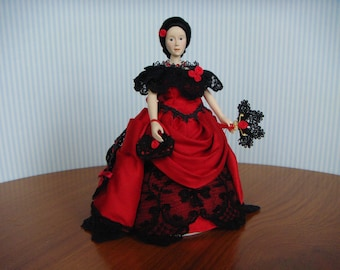 A period dolls house lady doll in a red and black ballgown