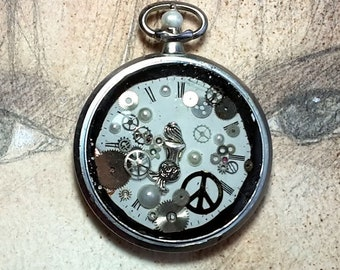 Unisex steampunk pendant; little mythic mermaid, 1 peace symbol make love not war, cogs and dial, resin in an old pocket watchcase