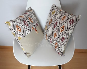 Cushion cover with ethnic geometric patterns on linen-colored background