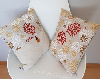 Cushion cover with patterns of flowers and rosettes in natural tones on a linen-colored background