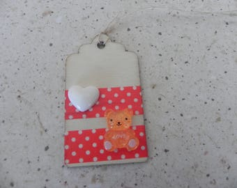 A wooden tag with a teddy bear measuring 7 x 4 cm