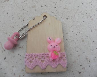 A wooden tag decorated measuring 7 x 4 cm
