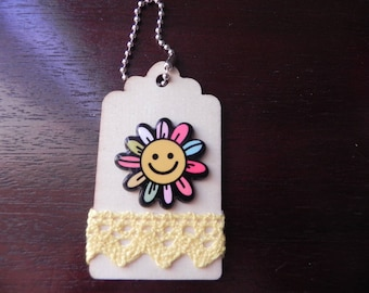 A wooden tag decorated with a daisy colored measuring 7 x 4 cm