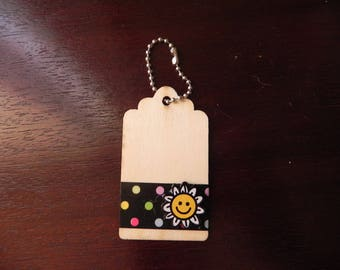 A wooden tag decorated with a daisy measuring 7 x 4 cm