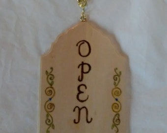 Open/closed reversible wood burned sign decorated with curls, swirls and leaves on pine, embellished with colored crystals.