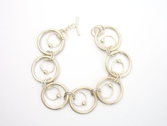 Armband aus Sterling Silber mit verschieden großen massiven Silberringen als Kettenglieder und kleinen Silberkugeln als Unikat in Handarbeit