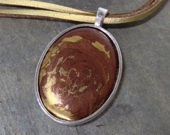 A brown and gold mixed enamel pendant