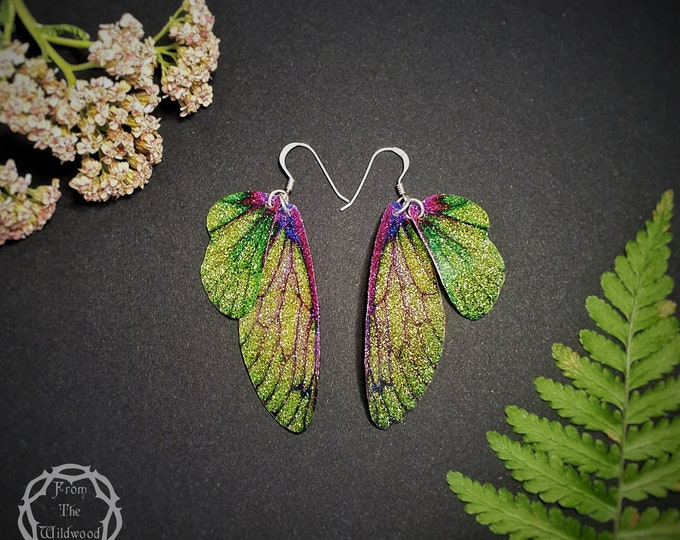 Featured listing image: Green and purple sparkle fairy wing earrings. Medium iridescent sparkle faerie wings on a choice of ear wires.