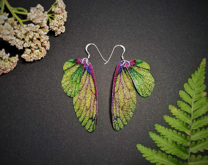 Featured listing image: Green and Purple Sparkle Fairy Wing Earrings. Medium iridescent sparkle faerie wings on sterling silver ear wires.