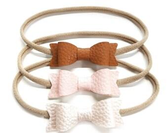 Baby bows, shades of blush, metallic shades, Vegan Leather headbands, baby headbands, vanaguelite, hair accessories, baby headbands.