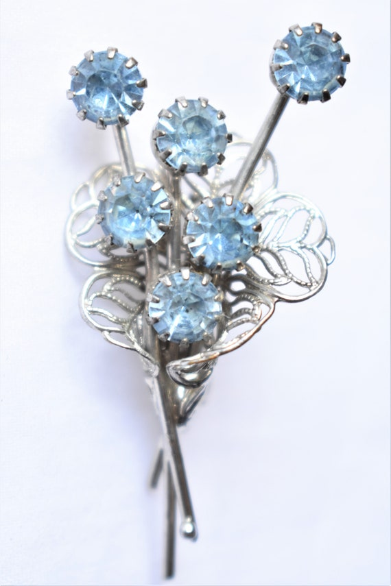 Light blue rhinestone mid century modern flower brooch in silver tone metal