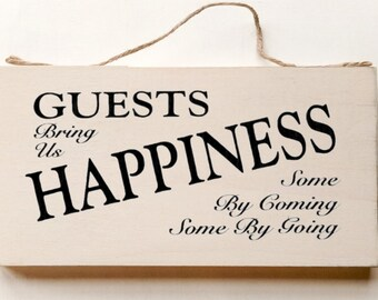 Wood sign saying: Guests Bring Us Happiness, Some by Coming, Some By Going