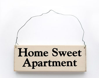 Wood Sign Saying 'Home Sweet Apartment' White Wood Sign With Black Lettering.
