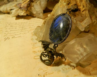 Labradorite in a cocoon of leather and her dragon pendant.