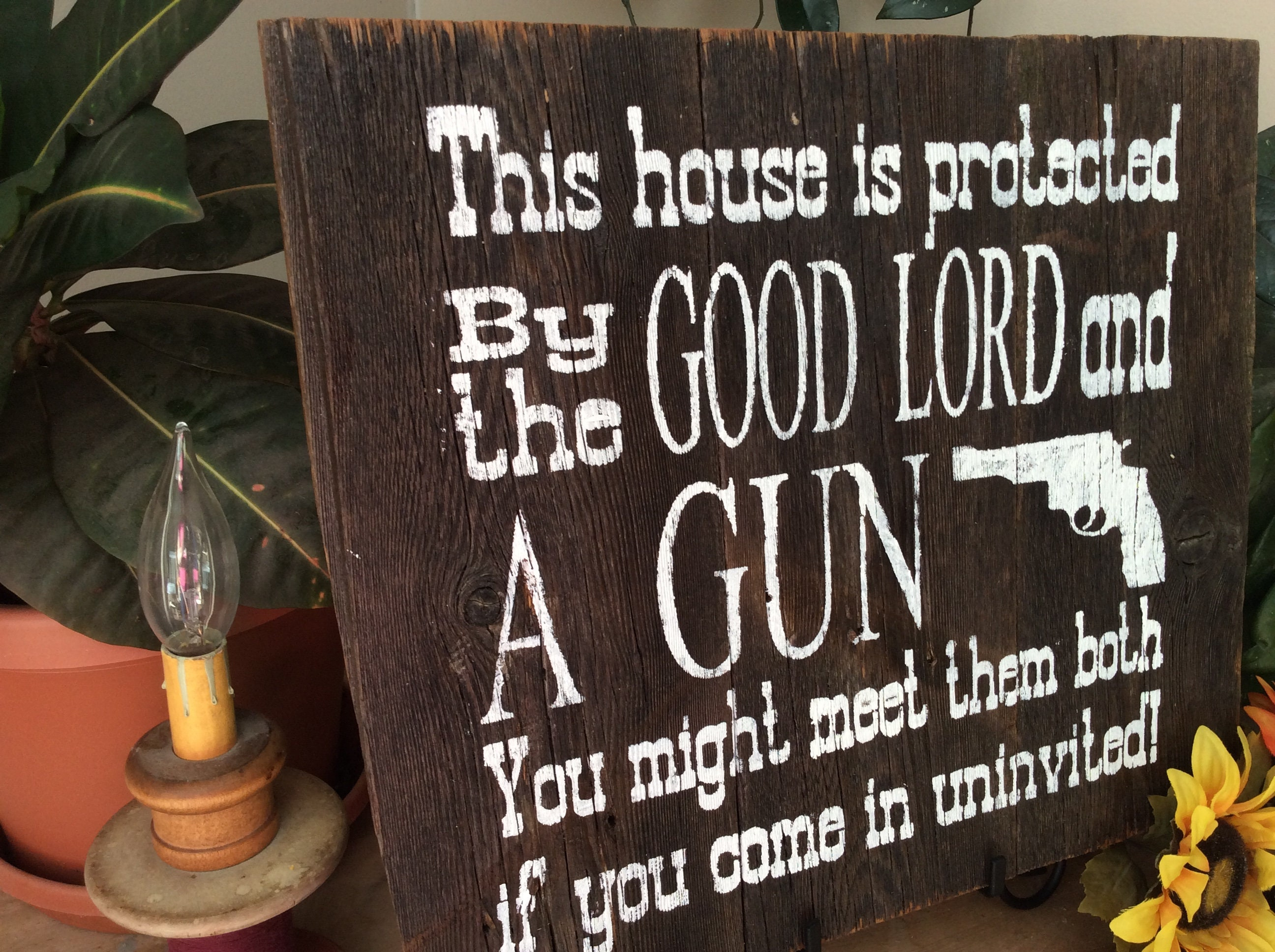 western sign this house is protected by good lord and a gun