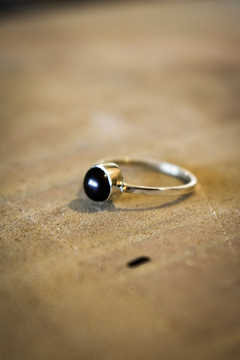 Silver ring set with a black cultured pearl.
