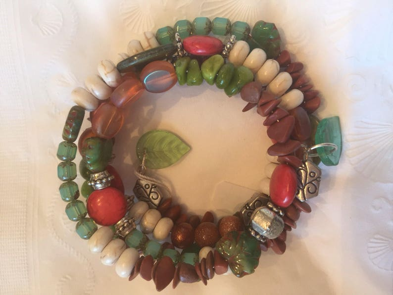 browns Silver accents. Boho beaded wrapped bracelet in reds in 4 layers greens