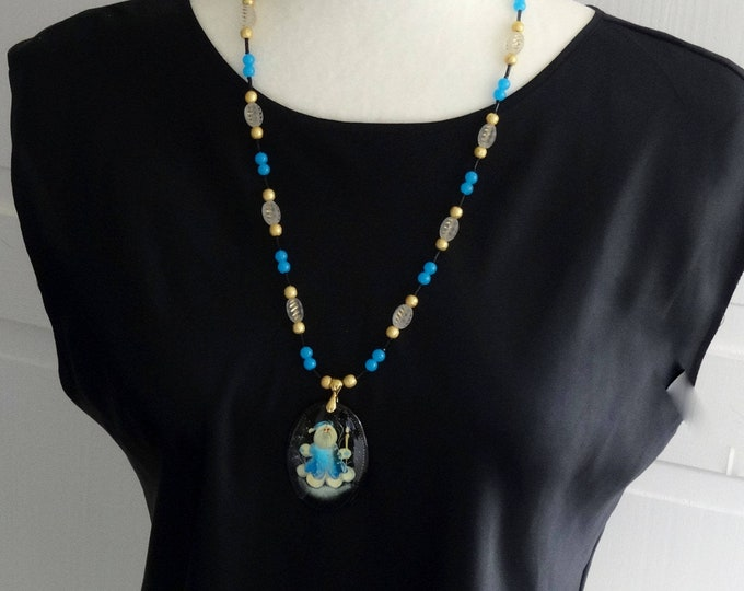 Christmas Necklace made of Black, White and Blue Glass Beads and Gold Metal Beads with Old World Santa Paper Mache Pendant