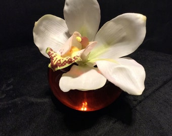 White Orchid bud in coloured glass container.